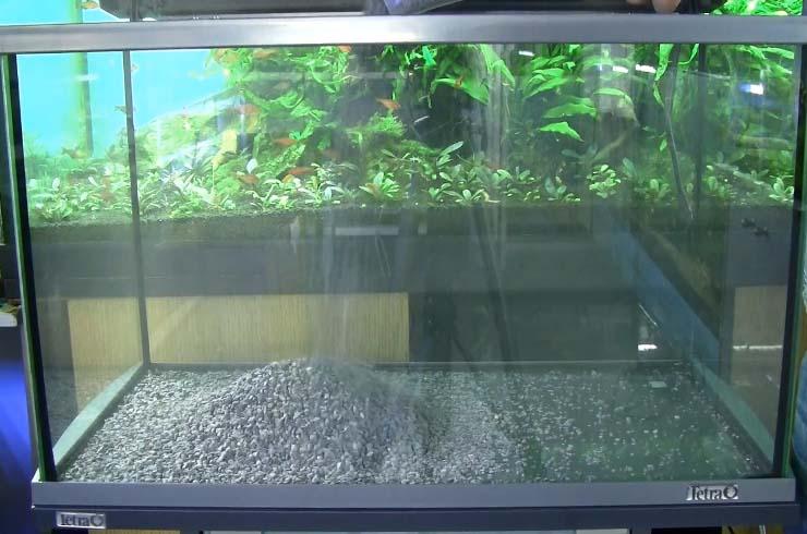 На дно аквариума укладываем темную гальку